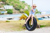 stock photo of tire swing  - Adorable little girl having fun on tire swing on summer day - JPG