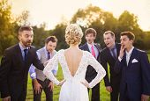 stock photo of mans-best-friend  - Portrait of surprised groomsmen looking at beautiful bride outside - JPG