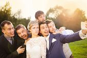 foto of mans-best-friend  - Outdoor portrait of beautiful young bride with groom and his friends taking selfie - JPG
