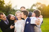 stock photo of mans-best-friend  - Outdoor portrait of beautiful young bride with groom and his friends taking selfie - JPG
