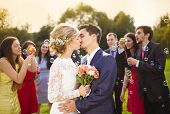 foto of blowing  - Young newlyweds kissing and enjoying romantic moment together at wedding reception outside - JPG