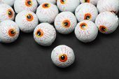 stock photo of gruesome  - Chocolate candy eyeballs arranged as a background for Halloween - JPG