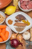 stock photo of tagine  - Ingredients for a Moroccan tagine dish with chick peas lamb carrots lemon onion cinnamon star anise - JPG
