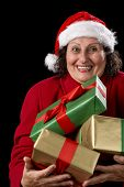stock photo of gold tooth  - Delighted female pensioner with Santa Claus cap and red coat is carrying three Christmas gifts close to her chest - JPG
