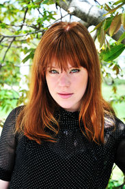 stock photo of freckle face  - spring redheaded girl under the green tree - JPG