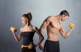 stock photo of weight-lifting  - Young man and woman in sport clothes lifting weights - JPG