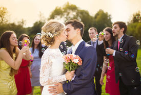picture of marriage ceremony  - Young newlyweds kissing and enjoying romantic moment together at wedding reception outside - JPG