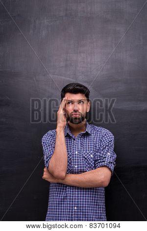 Dissatisfied casual man is on blank chalkboard background