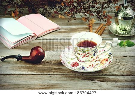 Vintage cup with smoking pipe and notebook