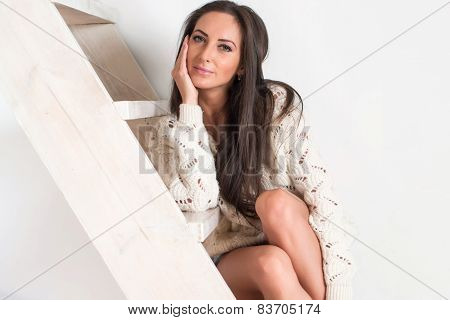 Amazingly beautiful brunette sexy charming woman in white sweater is sitting at the stairs home.