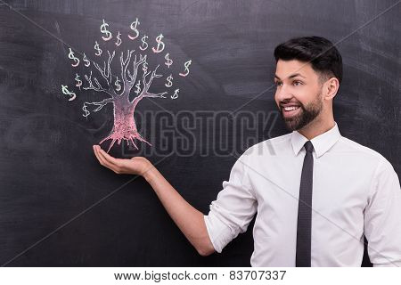 Young businessman and dollar tree painted on chalkboard