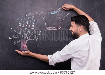 Businessman watering dollar tree painted on chalkboard