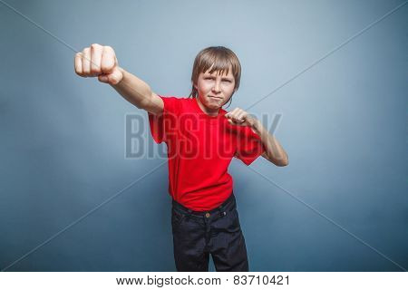 Boy, teenager, twelve years  red  in shirt, red showing  fists h