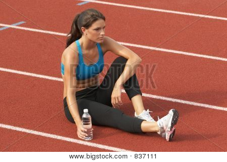 Young Woman in Sports Bra with Water Bottle on Track Relaxing