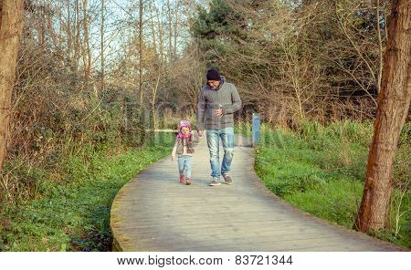 Father and daughter walking together holding hands