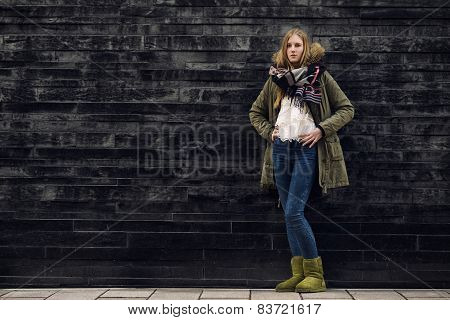 Woman In Winter Outfit In Front Old Gray Wall