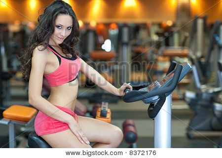 Girl  Is Cycling In Fitness Hall