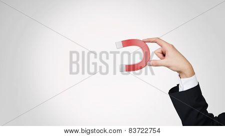 Hand Holding Red Magnet