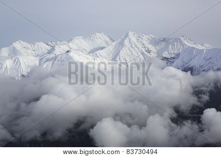 Tops of snow-capped mountains in the clouds.