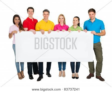 Multiethnic Group Of Friends Showing Blank Billboard