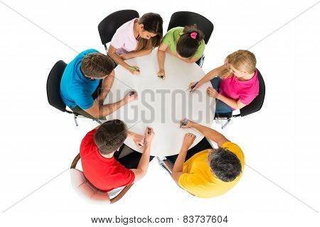 Group Of Friends Writing On Desk
