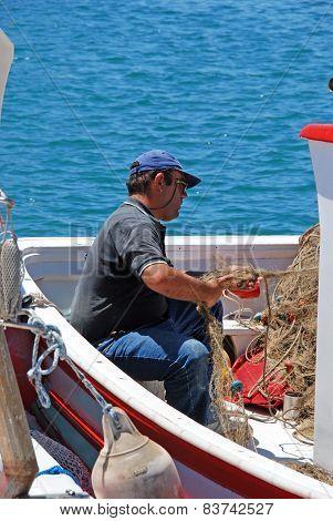 Spanish fisherman tending his nets.