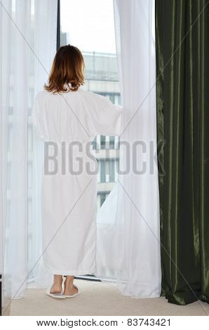 Back Portrait of a woman in a white bathrobe in front of a window