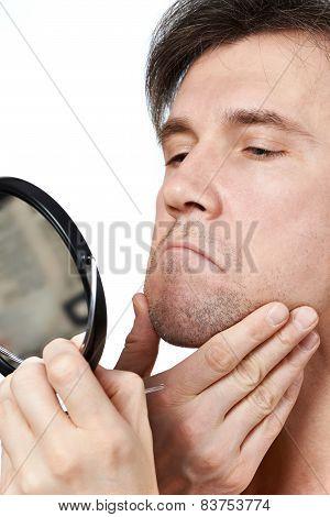 Unshaven Man Looks In The Mirror
