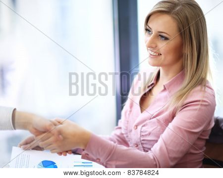 Business woman smiling and doing a handshake in the office