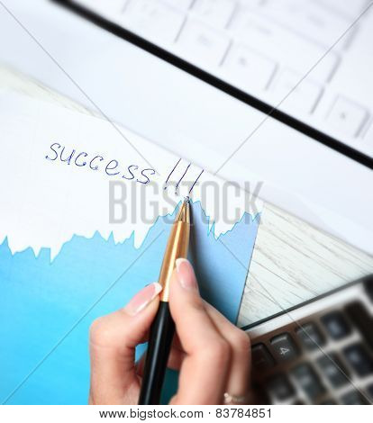 Businesswoman's hand with pen write word Success