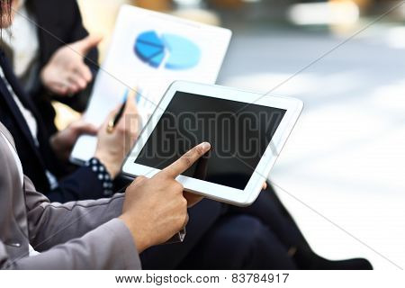 Closeup two modern business people working with digital tablet