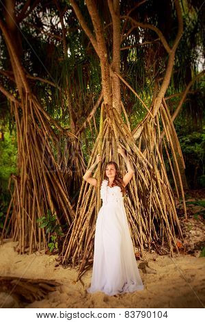 Bride Smiling Against Strange Roots Of Tropical Plant