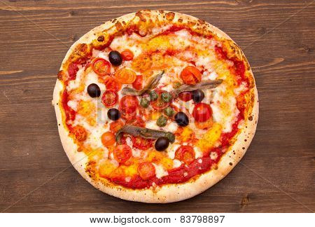 Pizza with anchovies and olives on wood from above