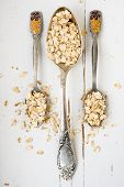 stock photo of tablespoon  - Three tablespoons of oatmeal lying on a white wooden background - JPG