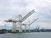 stock photo of oversize load  - Large container ship unloading cranes in a harbor - JPG