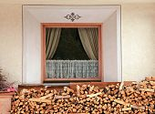 picture of firewood  - Window and pile of firewood stacked up in front of house in the Alps - JPG