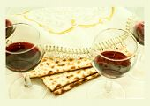 stock photo of hebrew  - the symbols of the Easter holiday three pieces of matzah four glasses filled with wine white cloth with embroidery and font on the Hebrew Pesach on a white background isolated - JPG