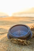 image of longitude  - Ancient compass on the sand at the Beach Sunrise nature background  - JPG