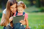 foto of fall day  - Beautiful mother and kid girl playing at tablet pc outdoors in fall - JPG