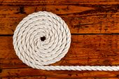 picture of coil  - Coiled white rope on a highly textured wooden background - JPG