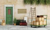 foto of old suitcase  - Exterior of an old house with cart full of boxes suitcases ready for the move  - JPG