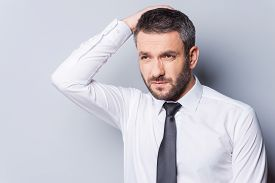 foto of tied hair  - Frustrated mature man in shirt and tie holding hand in hair and looking away while standing against grey background - JPG