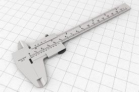 foto of vernier-caliper  - Metal Vernier Caliper over Graph Paper on a white background - JPG