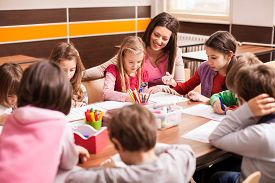 picture of classroom  - Children boys and girls sitting together around the table in classroom and drawing - JPG