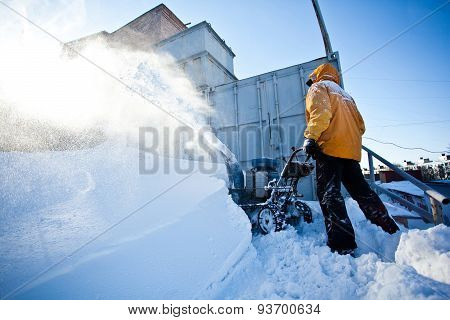 Man in yellow winter jacket cleaning garage path near his house with snow throwing machine