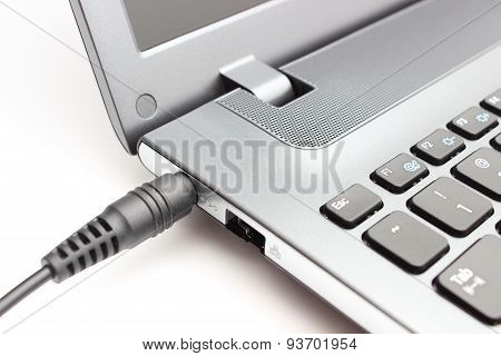 Plug Adapter Being Connected To Laptop Computer