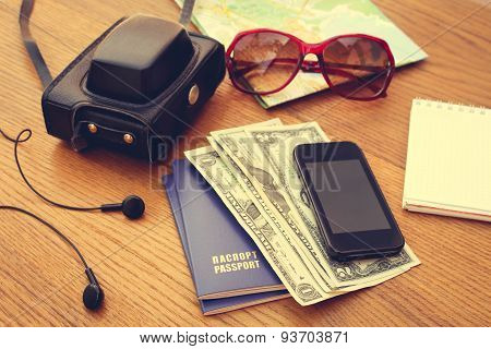 Travel set: passport, money, mobile phone, blank notebook, camera, road map, sunglasses, headphones.