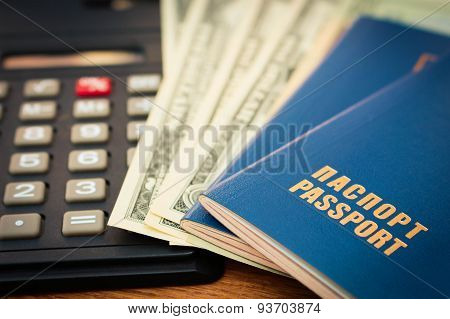 Closeup of a passport, calculator and dollars
