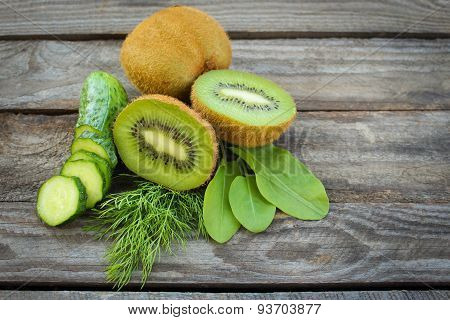 Green vegetables and fruits: kiwi, cucumber, dill, sorrel on wooden background.