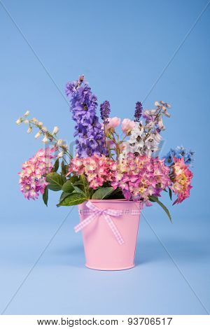 Mixed colorful garden bouquet in vase on blue background